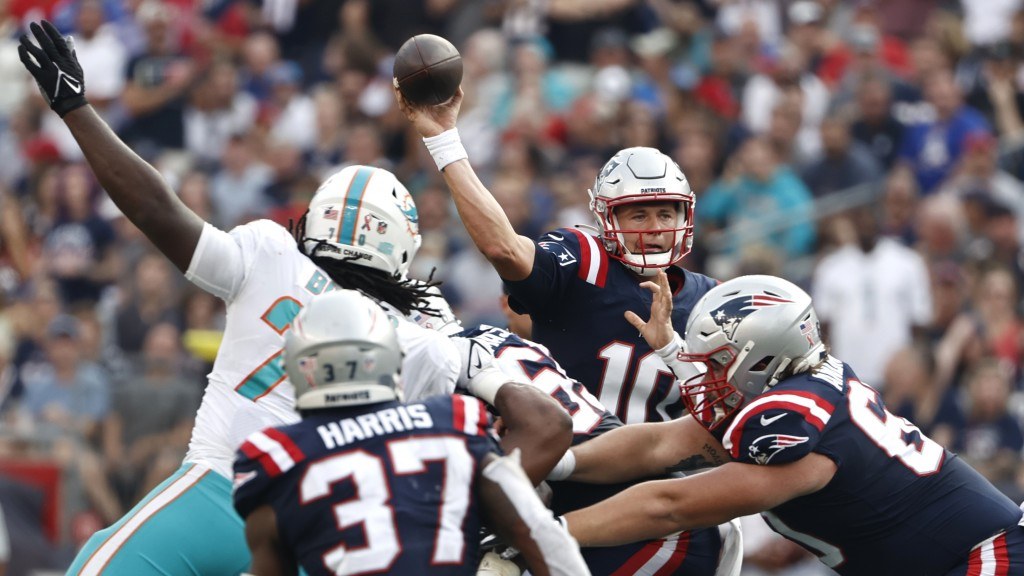 New England Patriots quarterback Mac Jones (10) passes under pressure during the first half of an NFL football game against the Miami Dolphins, Sunday...