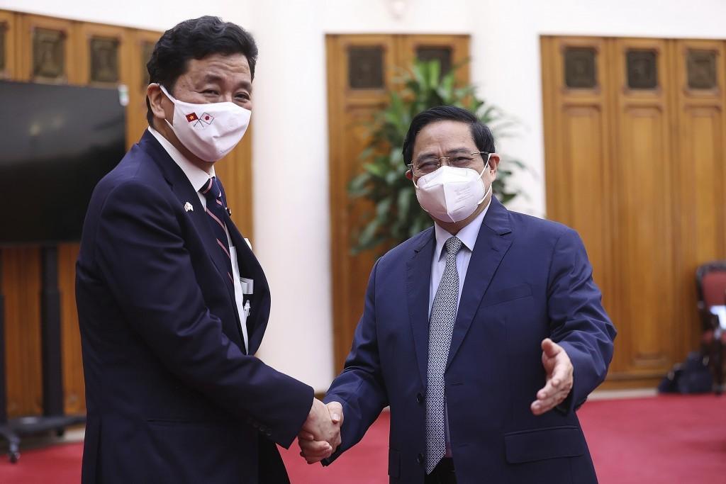 Vietnamese Prime Minister Pham Minh Chinh, right, and Japanese Defense Minister Nobuo Kishi shake hands in Hanoi, Vietnam Sunday, Sept. 12, 2021. Japa...
