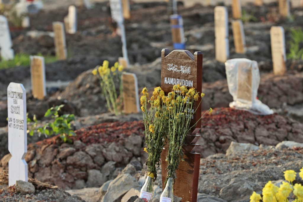 Flowers are laid on the grave of a COVID-19 victim at Rorotan Cemetery in Jakarta, Indonesia, Wednesday, Aug. 25, 2021. In the graveyard on Jakarta's ...