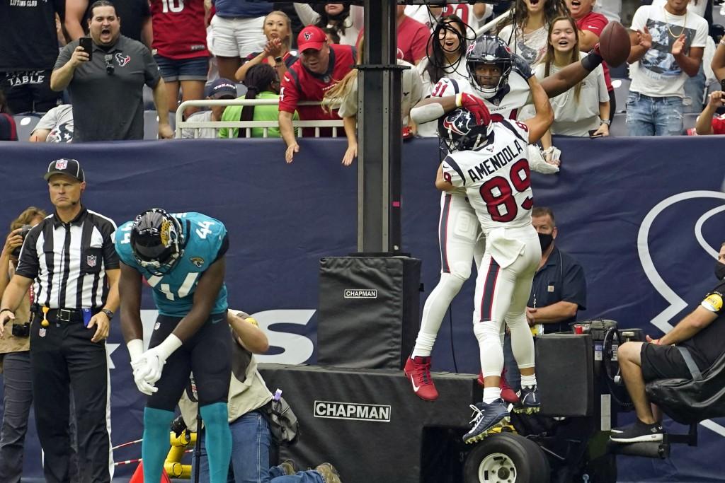 Houston Texans' David Johnson (31) celebrates his touchdown catch with Danny Amendola (89) as Jacksonville Jaguars linebacker Myles Jack (44) looks do...