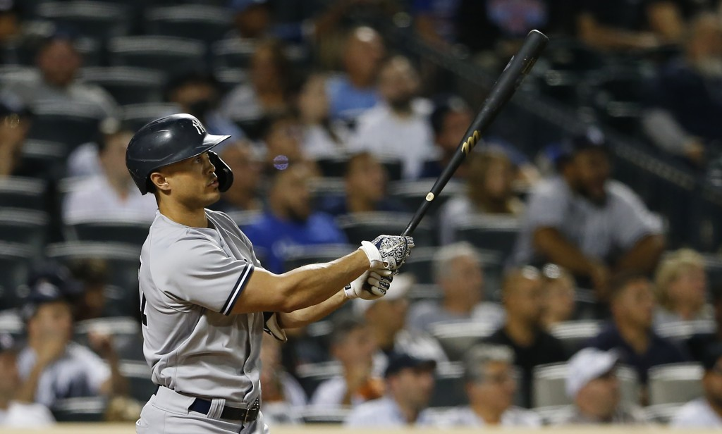 New York Yankees' Giancarlo Stanton watches his two-run home run against the New York Mets during the seventh inning of a baseball game, Sunday, Sept....