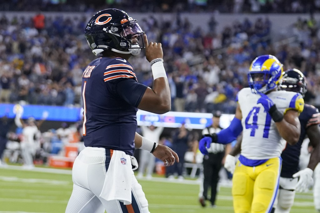 Chicago Bears quarterback Justin Fields reacts after scoring a touchdown during the second half of an NFL football game against the Los Angeles Rams, ...