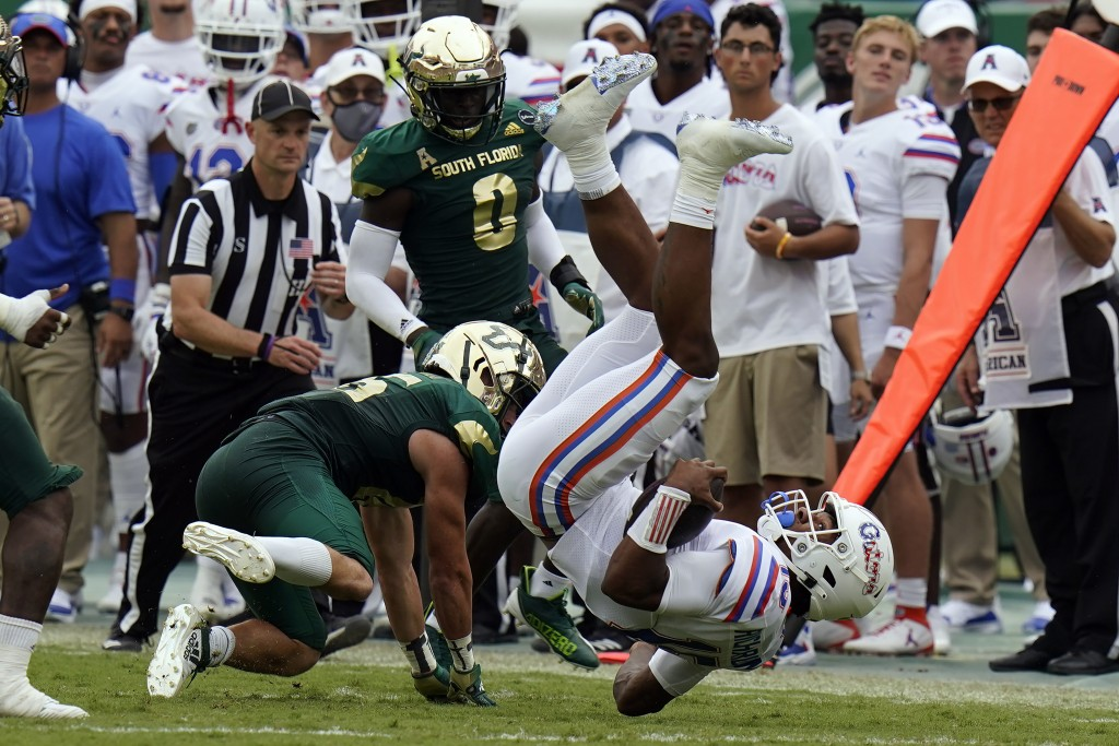 Florida quarterback Anthony Richardson (15) gets upended by South Florida safety Brock Nichols during the second half of an NCAA college football game...