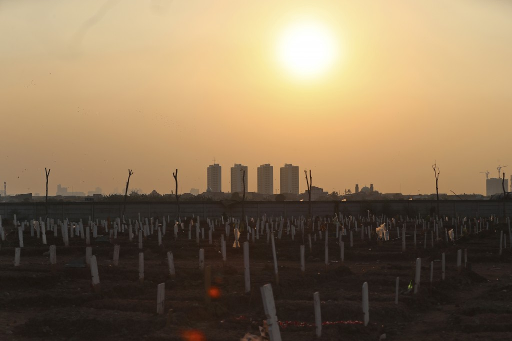 The sun sets over Rorotan Cemetery which was reserved for those who died of COVID-19, in Jakarta, Indonesia, Wednesday, Aug. 25, 2021. Jakarta governm...