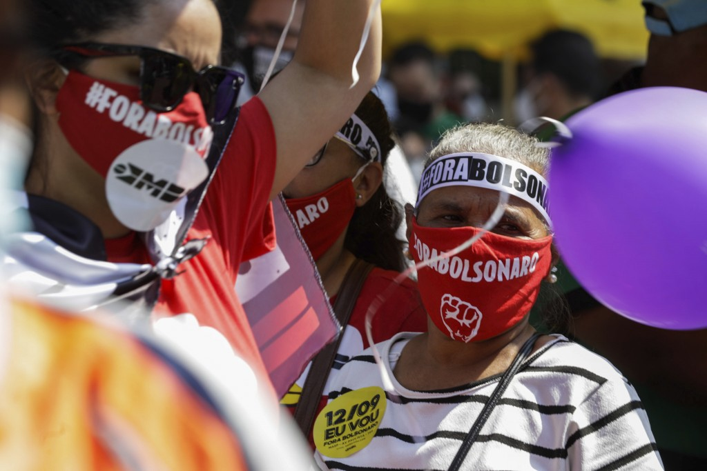 """A woman wears a mask with the words """"Bolsonaro out,"""" during a protest against Brazilian President Jair Bolsonaro, at Paulista Avenue, Sao Paulo, Brazi..."""
