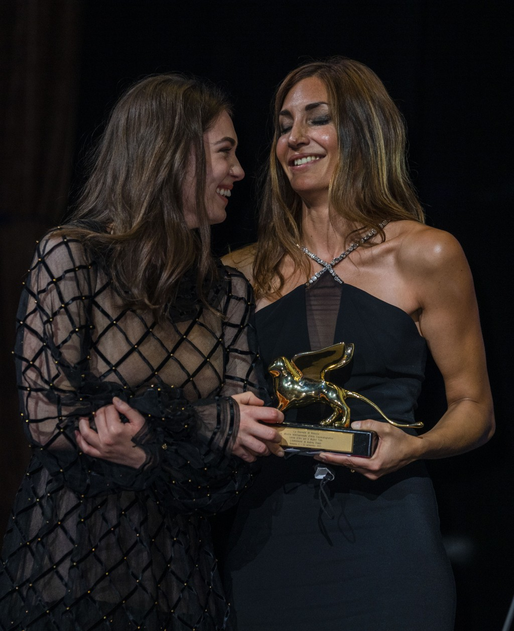 FILE - In this Sept, 11, 2021 file photo Anamaria Vartolomei, left, congratulates director Audrey Diwan as she holds the Golden Lion award for 'Happen...