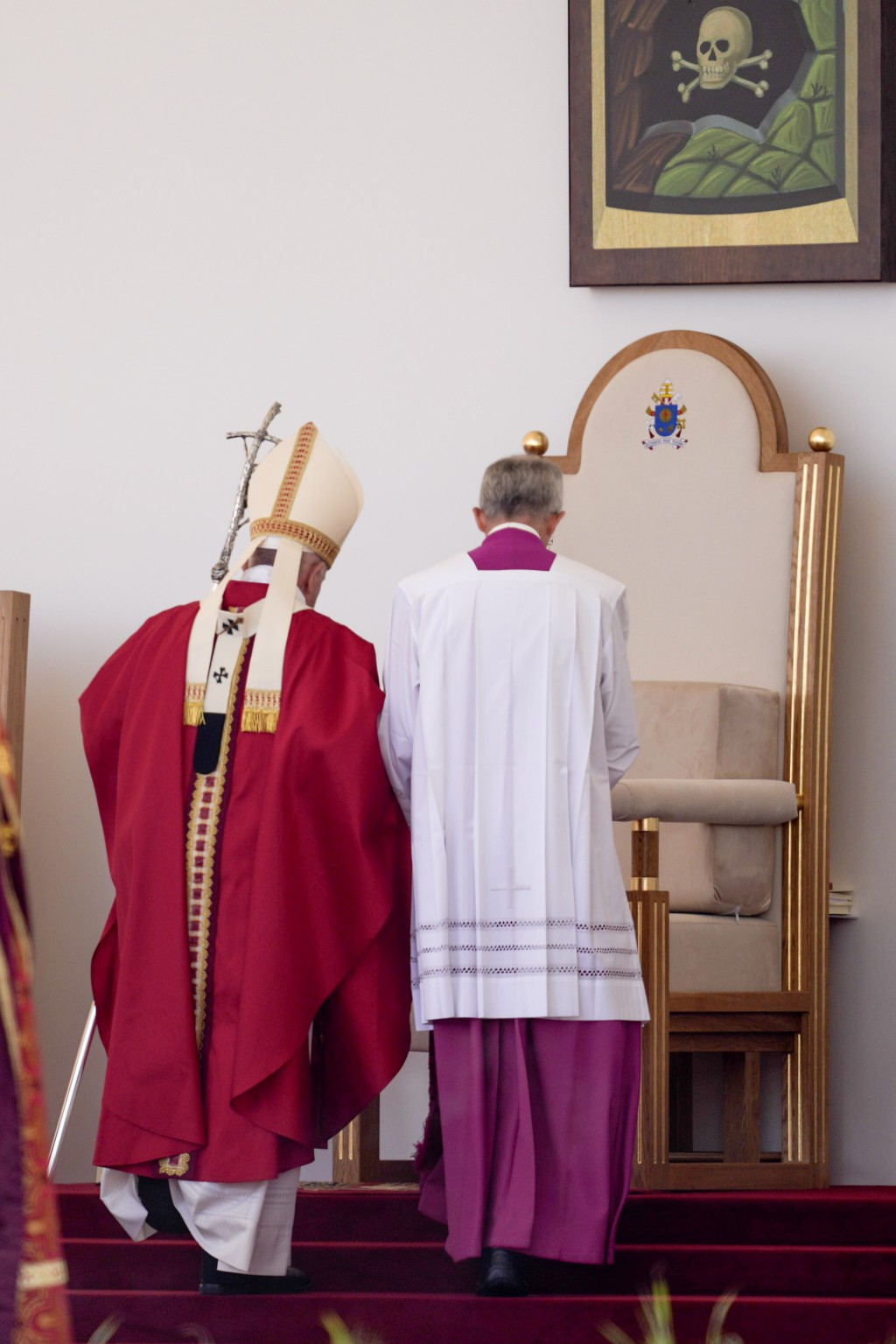 Pope Francis, left, is helped to his seat as he arrives to celebrate a Byzantine rite Mass at Mestska sportova hala Square, in Presov, Slovakia, Tuesd...