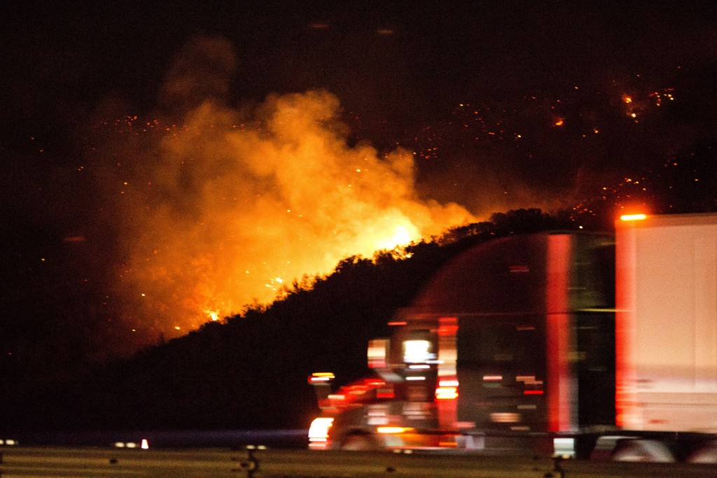 A vehicle passes by the burning Route fire, a brush wildfire off Interstate 5 north of Castaic, Calif., Saturday, Sept. 11, 2021. The wildfire near Ca...