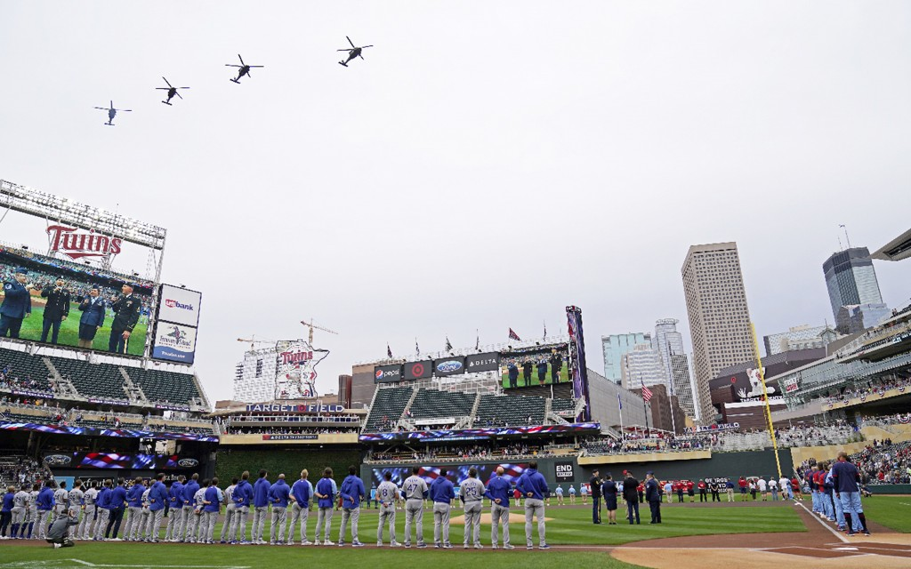Kansas City Royals players, left, and Minnesota Twins players, right, line up for the National Anthem and flyover of four Blackhawk helicopters over T...