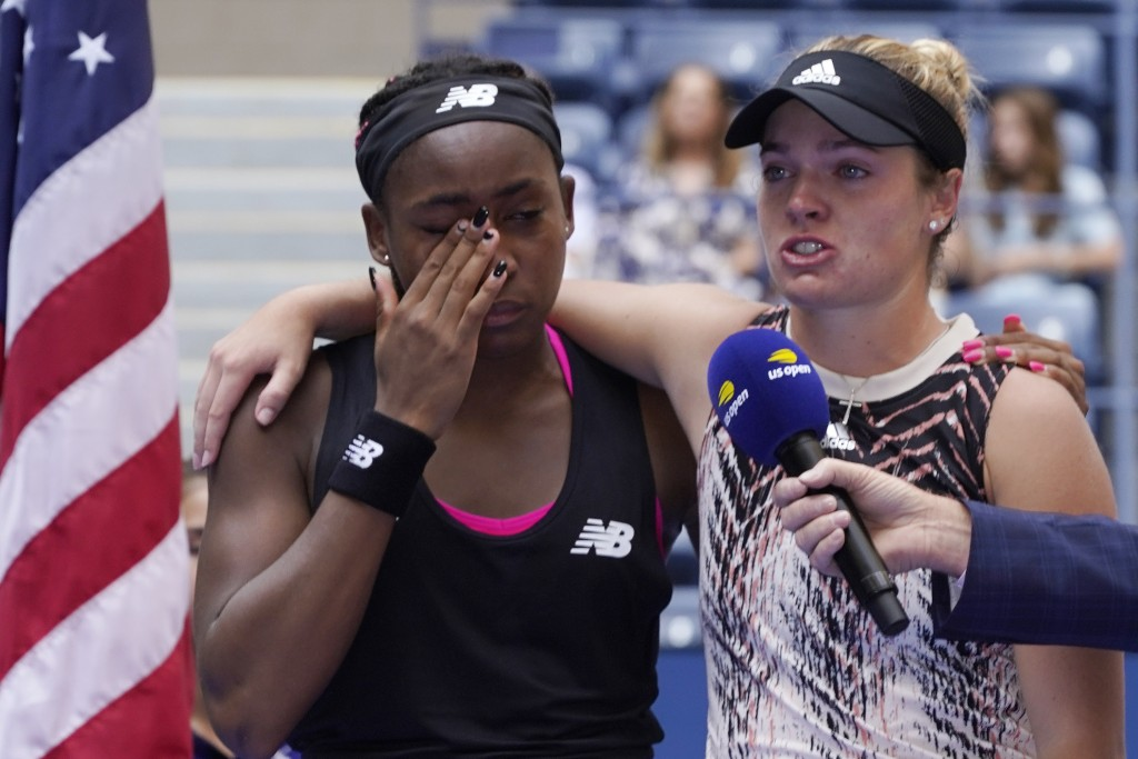 Coco Gauff, left, and Catherine McNally, both of the United States, become emotional as they speak to the crowd after losing to Shual Zhang, of China,...