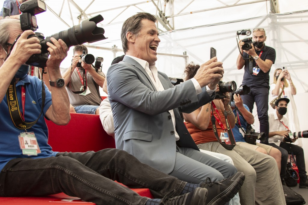 FILE - In this Sept, 3, 2021 file photo Josh Brolin, centre, takes photograph with his cell phone at the photo call for the film 'Dune' during the 78t...