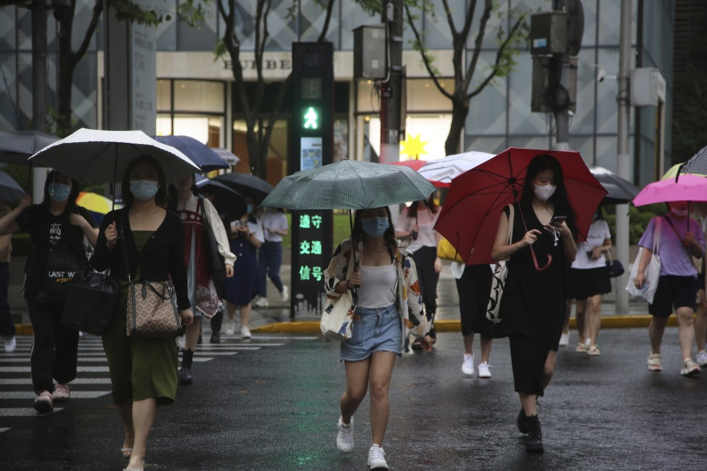 Residents using umbrellas cross an intersection in Shanghai, China, Tuesday, Sept. 14, 2021. Flights and train service were being canceled in Shanghai...