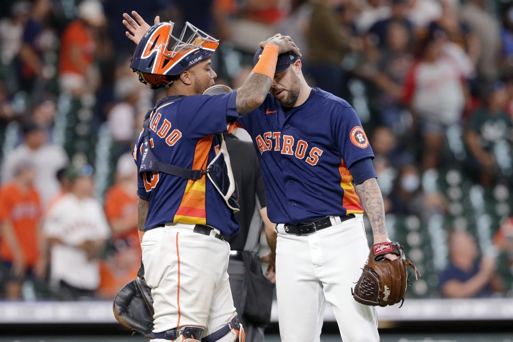 Houston Astros catcher Martin Maldonado, left, and closing pitcher Ryan Pressly, right, pat each other on the head after their 3-1 win over the Los An...