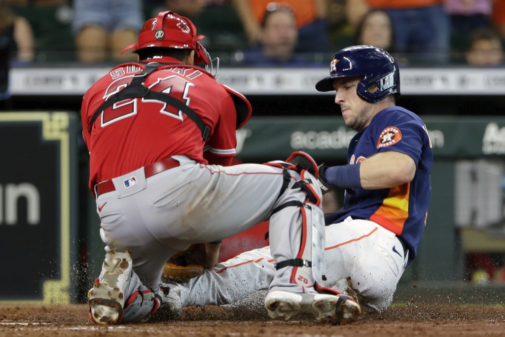 Houston Astros' Alex Bregman, right, is out at the plate on the throw to Los Angeles Angels catcher Kurt Suzuki, left, on the single by Yuli Gurriel d...