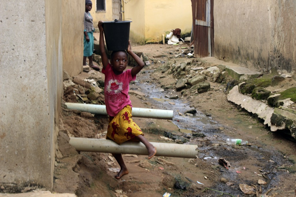 A girl carrying water on her head walks past sewage around houses in Abuja, Nigeria, Friday, Sept. 3, 2021. Nigeria is seeing one of its worst cholera...