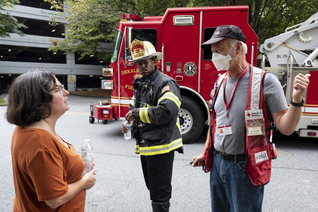 Dunwoody Mayor Lynn Deutsch, left, talks with a Red Cross worker as emergency workers respond following an apartment explosion, Sunday, Sept. 12, 2021...