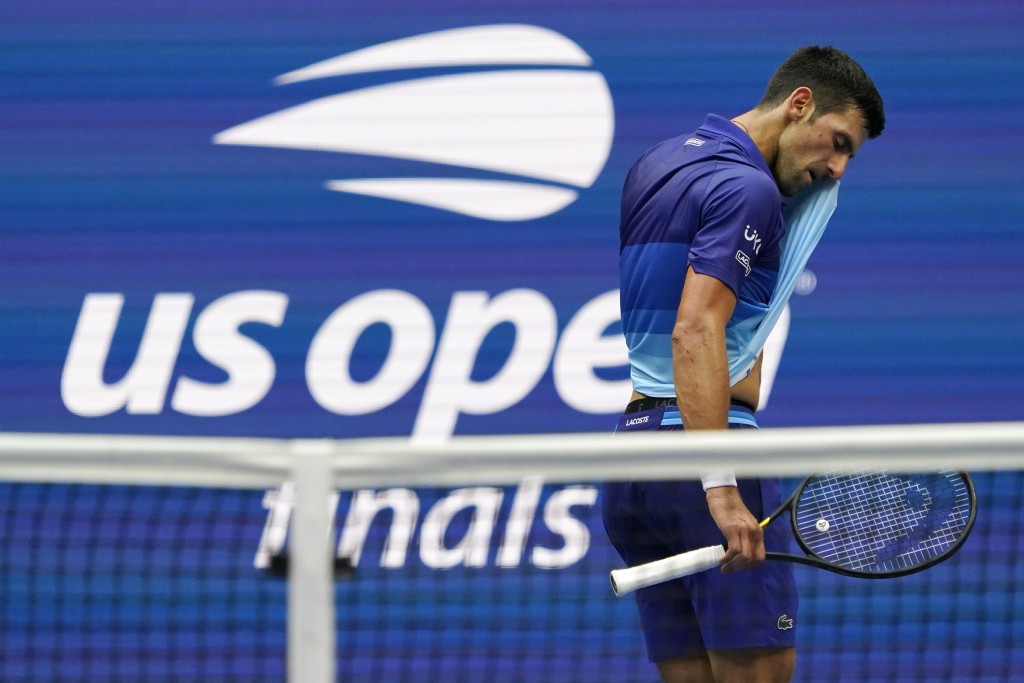 Novak Djokovic, of Serbia, wipes sweat from his face between serves from Daniil Medvedev, of Russia, during the men's singles final of the US Open ten...