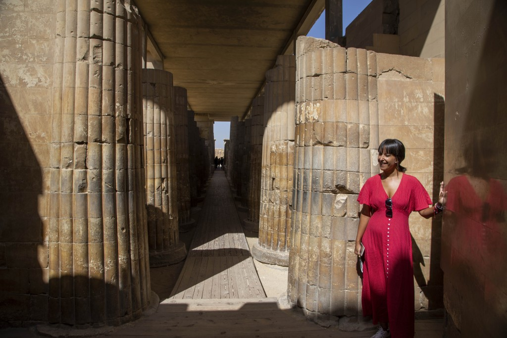 A tourist listens to a guide speak at the entrance of the southern cemetery of King Djoser, after its restoration, near the famed Step Pyramid, in Saq...