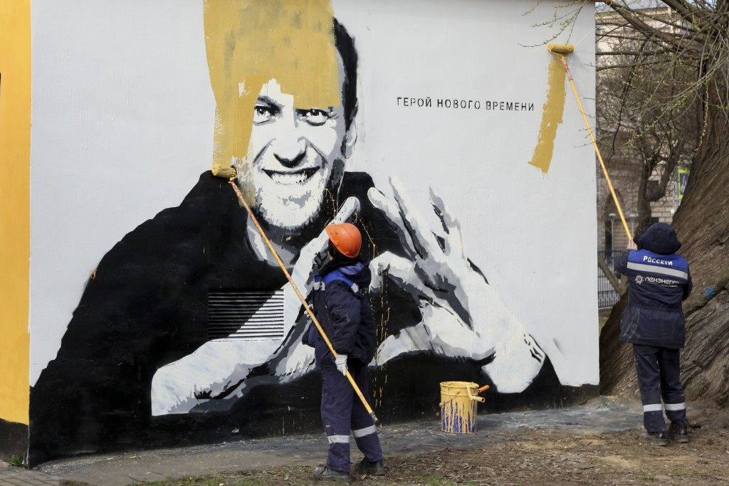 FILE - In this April 28, 2021, file photo, municipal workers paint over an image of Russia's imprisoned opposition leader Alexei Navalny in St. Peters...
