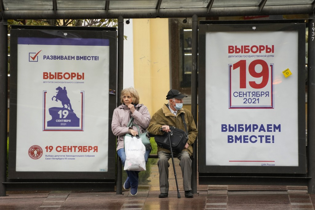 People sit at a bus stop decorated with election posters ahead of the parliamentary election to the State Duma, the Lower House of the Russian Parliam...