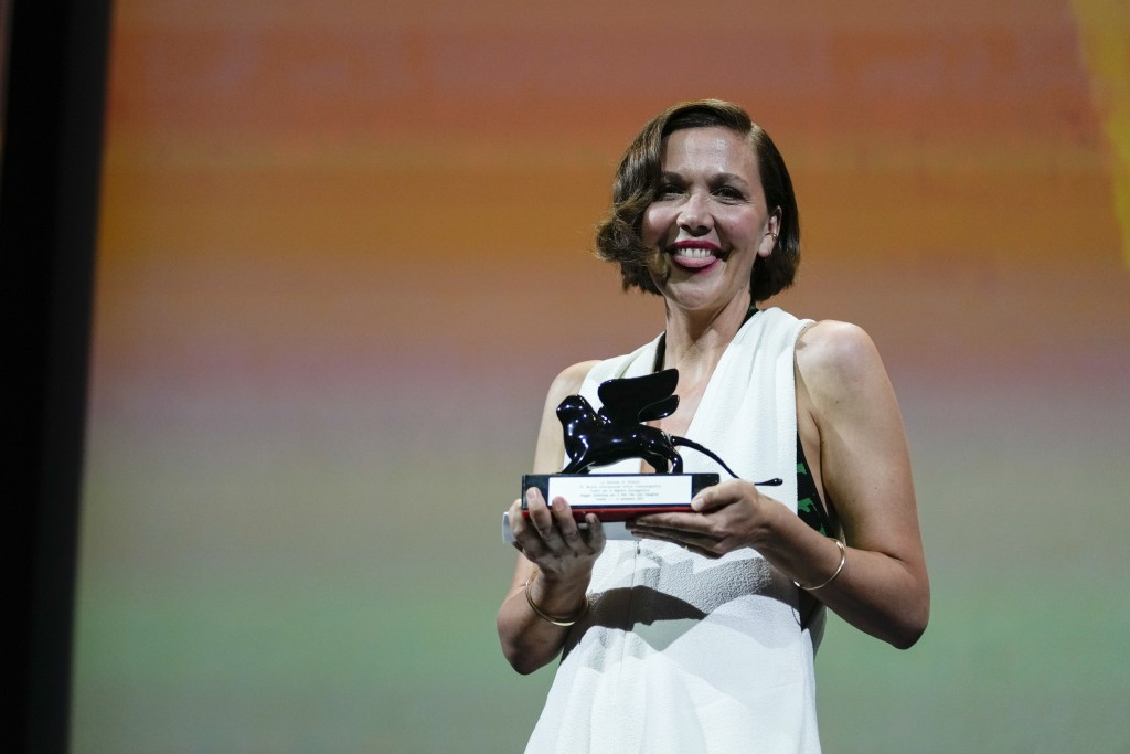 FILE - In this Sept, 11, 2021 file photo Maggie Gyllenhaal holds the Best Screenplay award for 'The Lost Daughter' onstage at the closing ceremony dur...