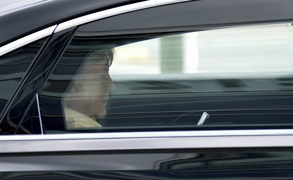 German Chancellor Angela Merkel looks at a mobile device as she leaves the headquarters of the German Christian Democratic Party (CDU) in a car in Ber...