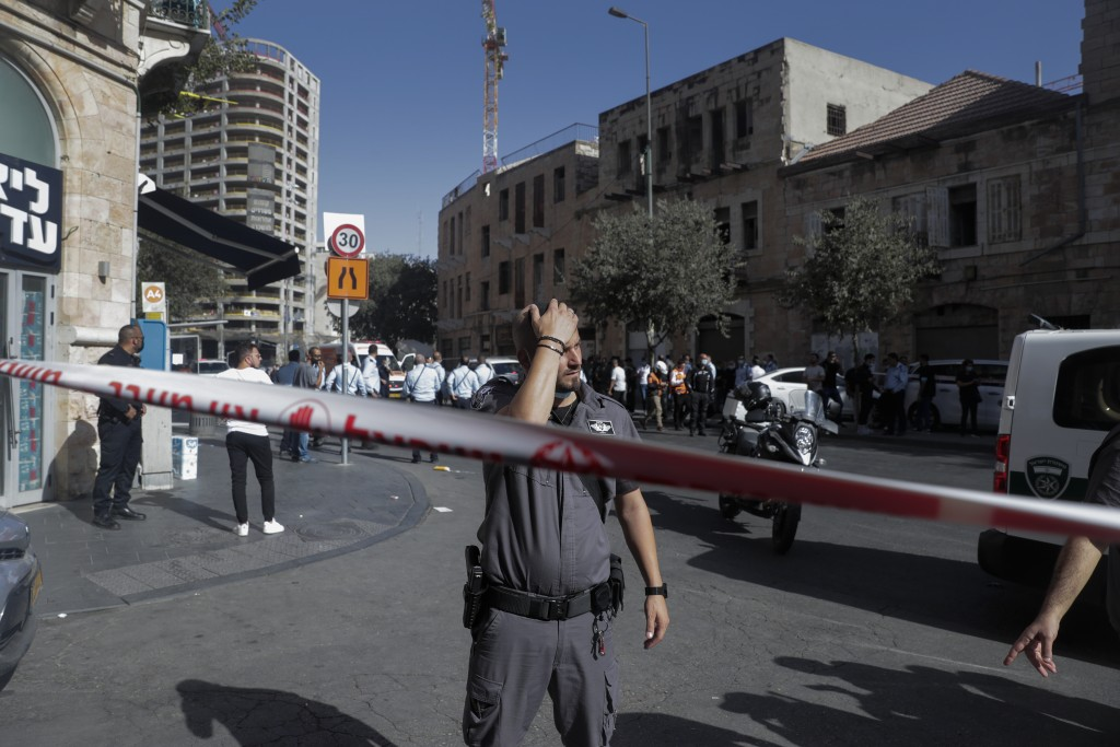 An Israeli Police officer stands guard at the site of stabbing attack in Jerusalem's Central Bus Station Monday, Sept. 13, 2021. Israeli paramedics tr...