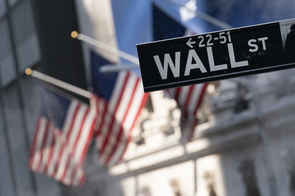 A sign for Wall Street hangs in front of the New York Stock Exchange, July 8, 2021. Stocks edged lower in morning trading, quickly reversing course af...
