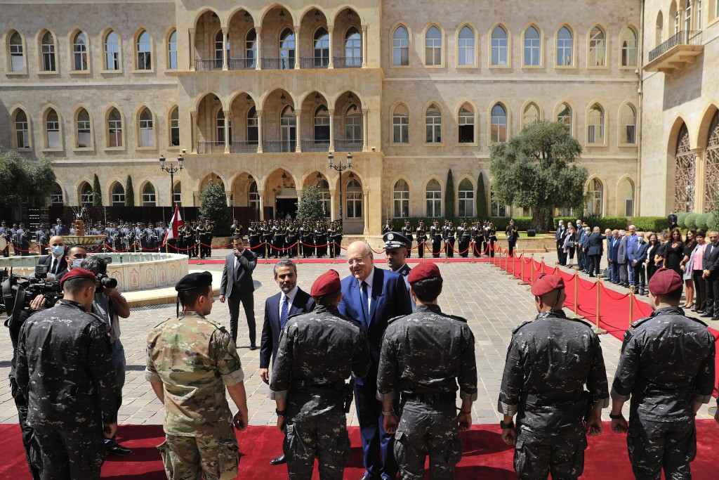 Lebanese Prime Minister Najib Mikati, center, shakes hands with officers from the government security forces during a ceremony marking his first day i...