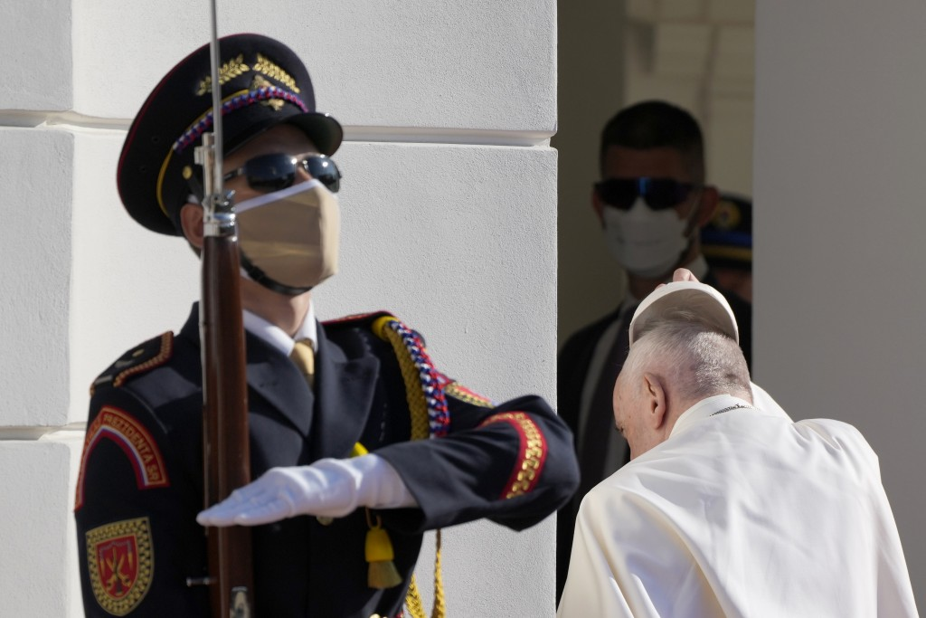 Pope Francis takes off his cap as he enters the presidential palace in Bratislava, Slovakia, Monday, Sept. 13, 2021. Francis is on a four-day visit to...