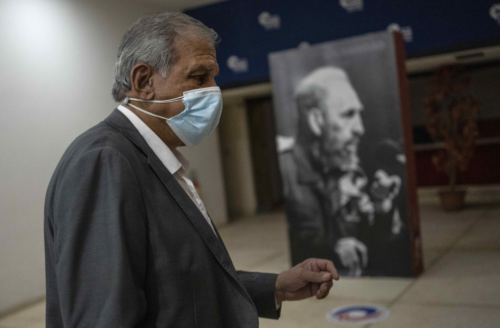 Mitchell Joseph Valdes Sosa, the director of the Cuban Neurosciences Center, walks past a photo of Fidel Castro before a press conference about sympto...