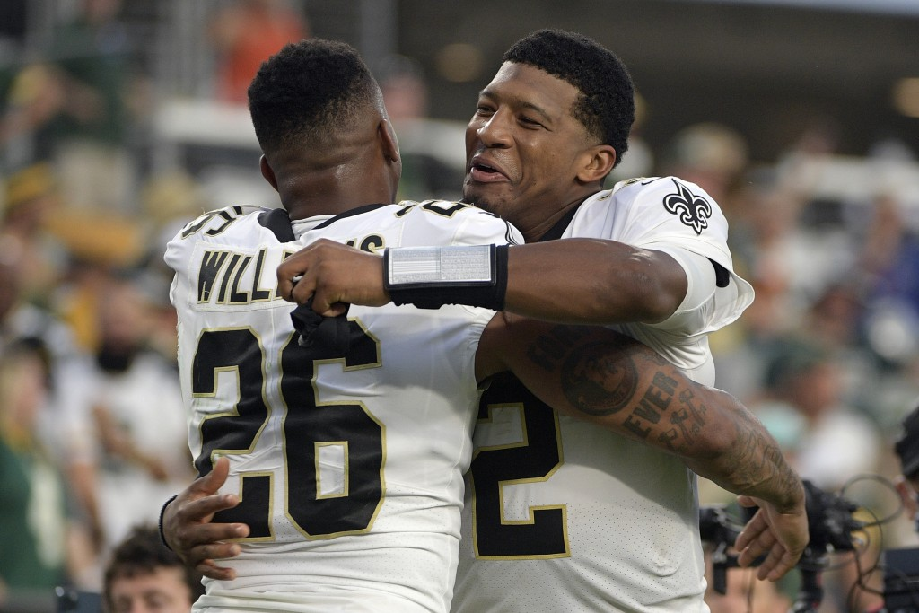 New Orleans Saints cornerback P.J. Williams (26) hugs quarterback Jameis Winston (2) after they defeated the Green Bay Packers in an NFL football game...