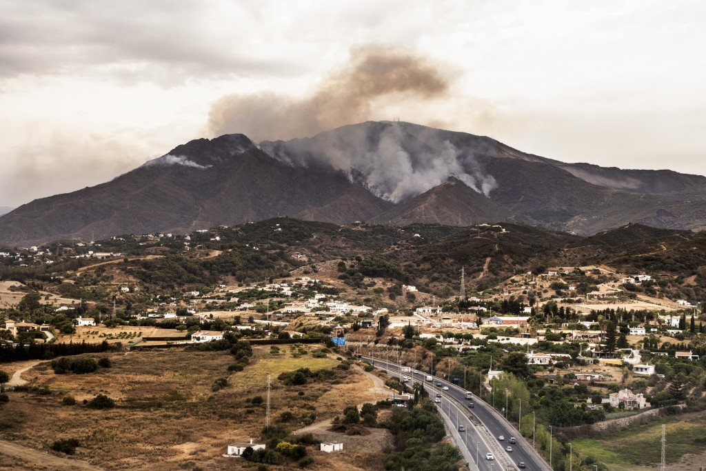 Smoke rises over smoking mountains, near the town of Jubrique, in Malaga province, Spain, Monday, Sept. 13, 2021. Firefighting crews in southern Spain...