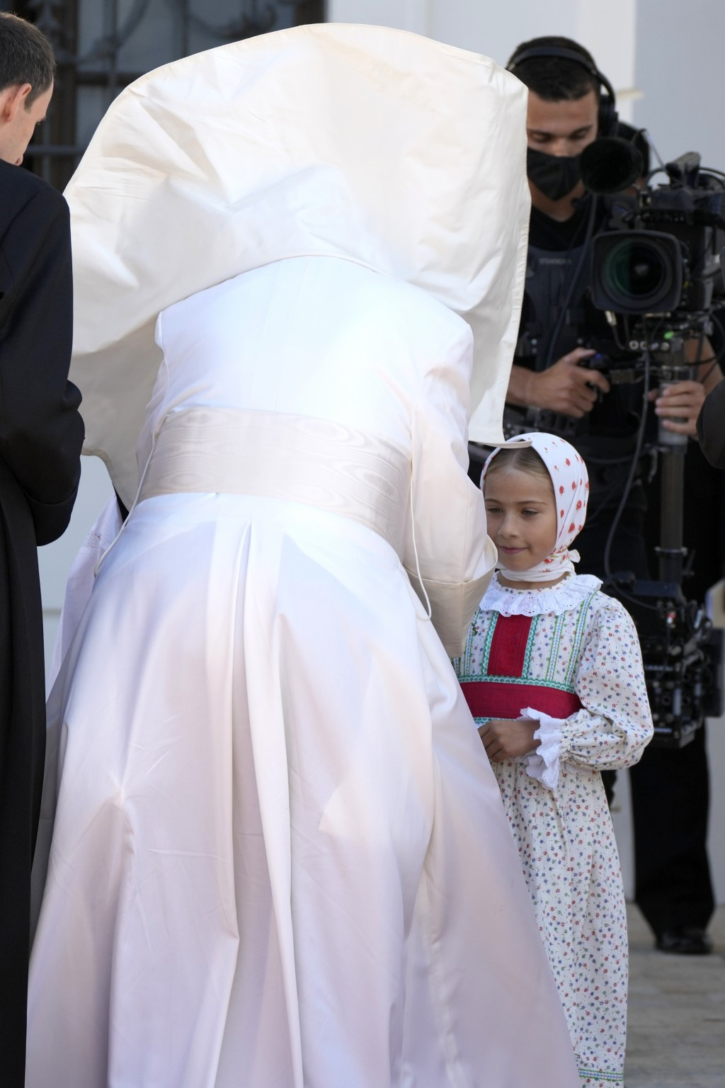 Pope Francis' mantle is blown by the wind as he greets a child during a welcoming ceremony at the presidential palace in Bratislava, Slovakia, Monday,...