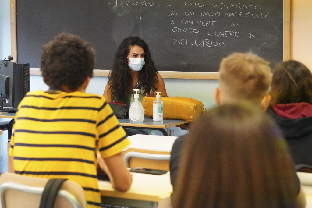 """A teacher and students wear face masks during a lesson, at the """"Isacco Newton"""" high school, in Rome, Monday, Sept. 13, 2021. After most of the last ye..."""
