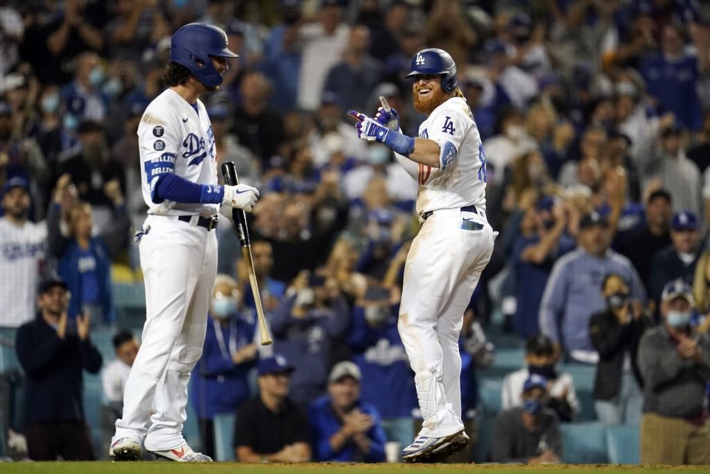 Los Angeles Dodgers' Justin Turner, center, celebrates his solo home run with Cody Bellinger during the seventh inning of a baseball game against the ...