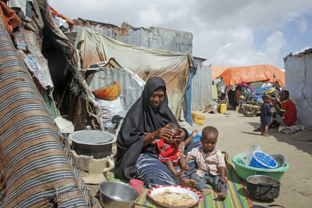Fatuma Mohamed, whose husband died of COVID-19 and struggles to raise two young children while earning money by doing laundry when she can, sits by he...