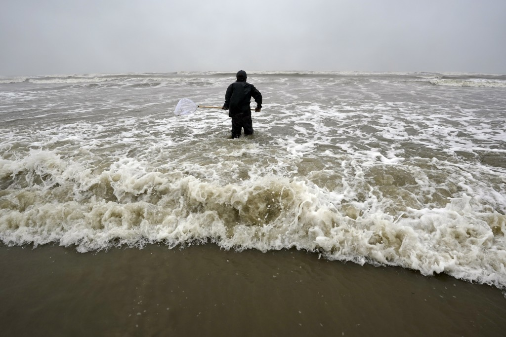 Daniel fishes in the Gulf of Mexico as winds from what was Hurricane Nicholas continue to push waves closer to shore Tuesday, Sept. 14, 2021, in Galve...