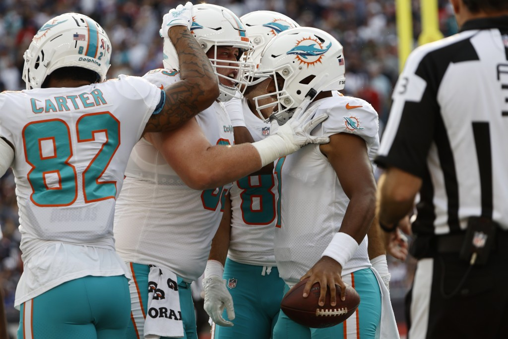 Miami Dolphins quarterback Tua Tagovailoa, right, is congratulated by teammates after his touchdown during the first half of an NFL football game agai...