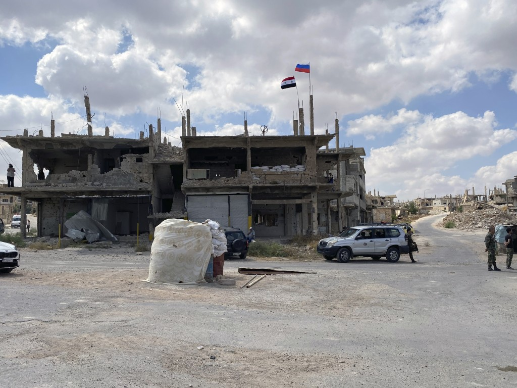 Syrian soldiers stand guard near a damaged building in the southern city of Daraa, Syria, Sunday, Sept 12, 2021. A Russian-negotiated deal went into e...
