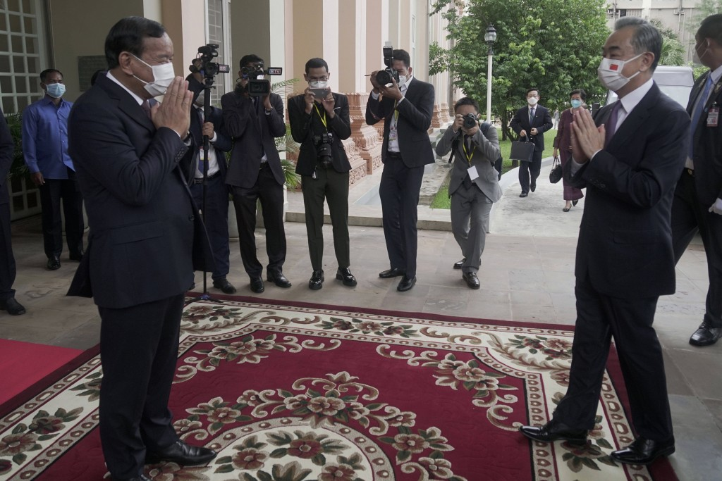 Chinese Foreign Minister Wang Yi, foreground right, greets with his Cambodian counterpart Prak Sokhonn, foreground left, in Phnom Penh, Cambodia, Sund...