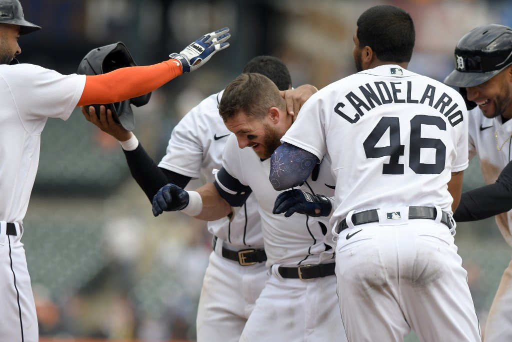 Detroit Tigers' Robbie Grossman, middle, is congratualted by teammates after walking in the winning run with the bases loaded against the Tampa Bay Ra...