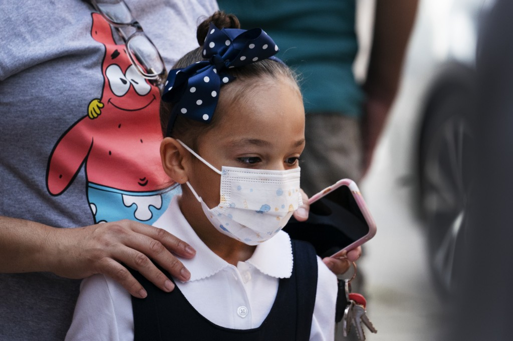 A girl arrives for the first day of school at Brooklyn's PS 245 elementary school, Monday, Sept. 13, 2021, in New York. Classroom doors are swinging o...