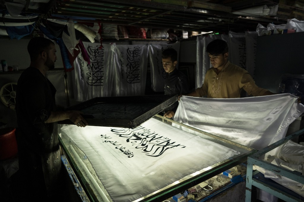 Workers hand print Taliban flags in a small workshop in Kabul's Jawid market, Afghanistan, Sunday, Sept. 12, 2021. The flag shop, tucked away in the c...