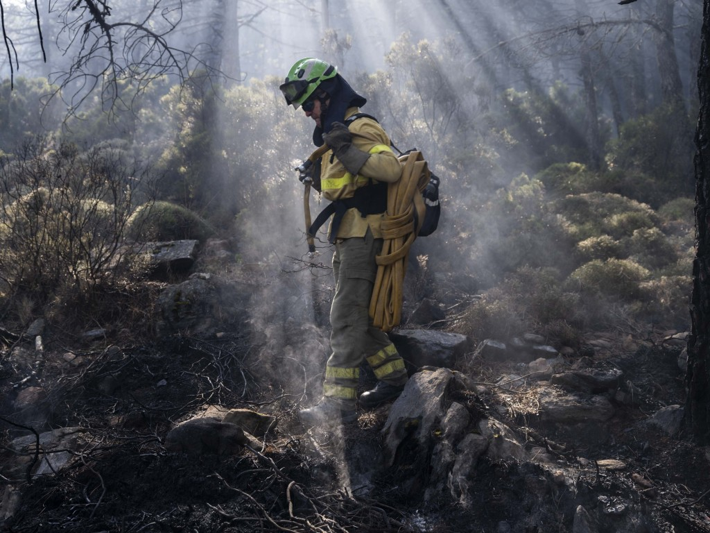 A forest firefighter works extinguishing hot spots in a wildfire near the town of Jubrique, in Malaga province, Spain, Saturday, Sept. 11, 2021.  Fire...