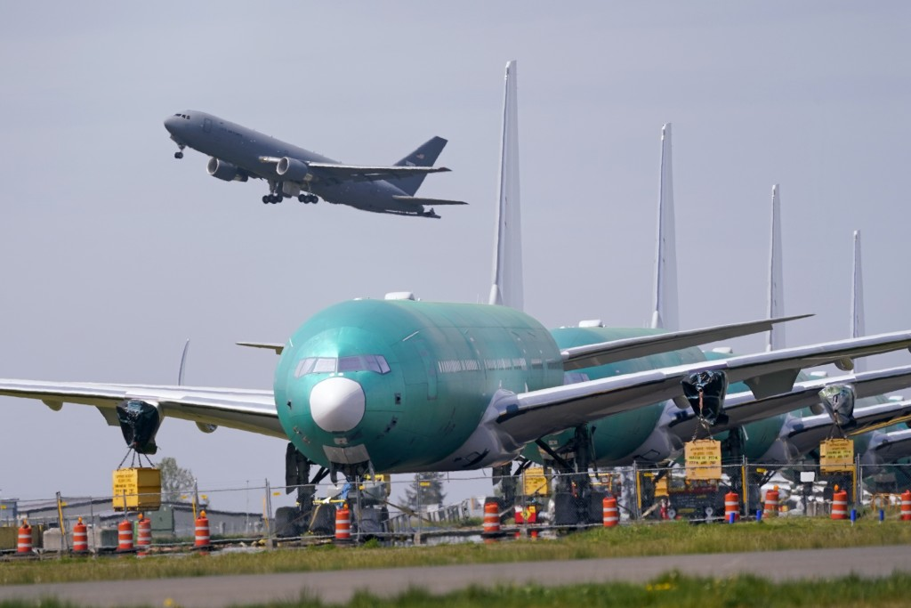 FILE - In this April 23, 2021 file photo, A U.S. Air Force KC-46A Pegasus jet takes off in view of a line of Boeing 777X jets parked nose to tail on a...