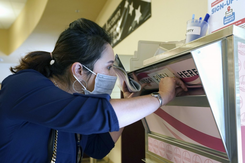 Amy Nguyen drops her recall ballot into the voting box at the Sacramento County Registrar of Voters office in Sacramento, Calif., Tuesday, Sept. 14, 2...