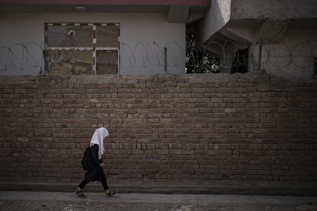 A girl walks to school before class in Kabul, Afghanistan, Sunday, Sept. 12, 2021. (AP Photo/Felipe Dana)