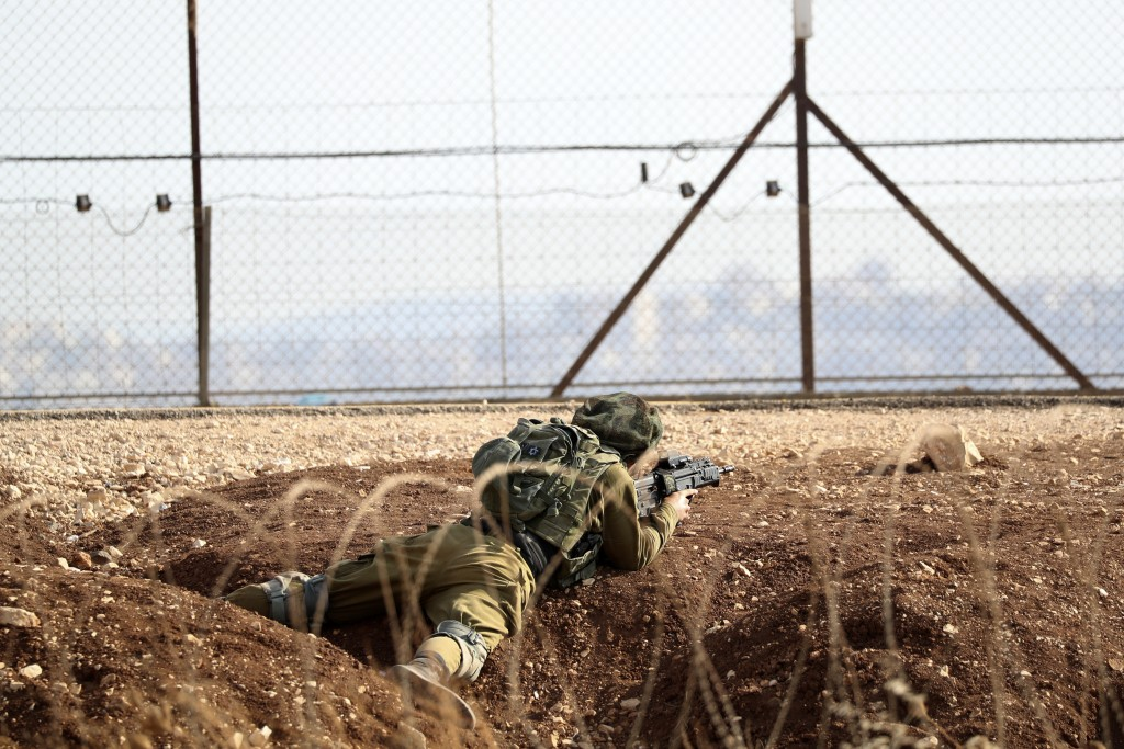 An Israeli soldier takes position along the border between the northern West Bank near Jenin and Israel as they search for two Palestinians who broke ...