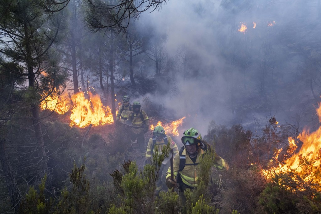 Forest firefighters work on a wildfire near the town of Jubrique, in Malaga province, Spain, Saturday, Sept. 11, 2021.  Firefighting crews in southern...